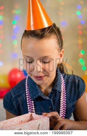 Girl looking at gift bag during birthday party at home