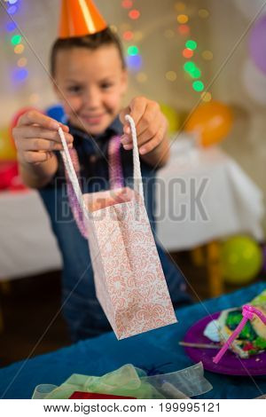 Girl holding a gift bag during birthday party at home