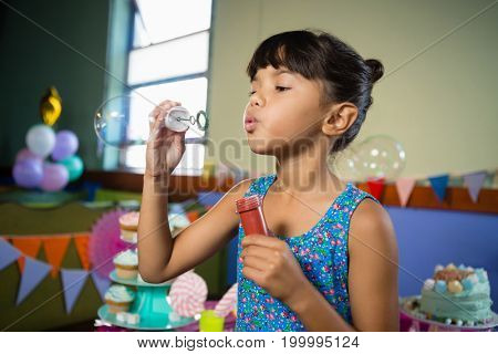 Girl playing with bubble wand during birthday party at home