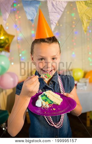 Portrait of girl eating cake during birthday party at home