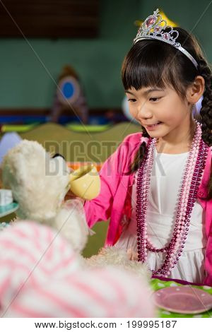 Girl playing with soft toy during birthday party at home