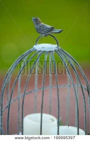 vintage beautiful birdcage with candles green and broun background