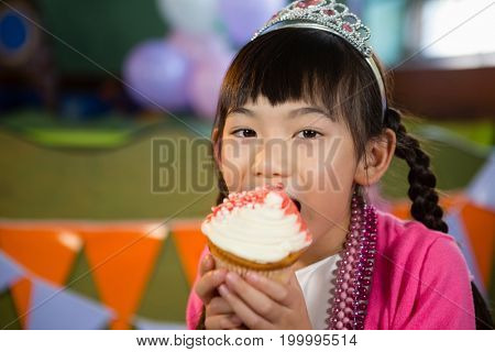 Portrait of girl having cupcake during birthday party at home