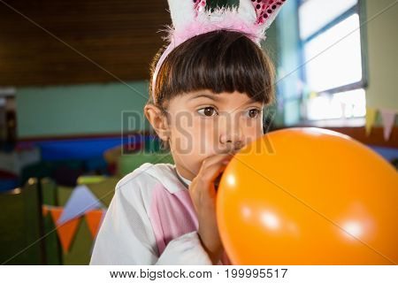 Adorable girl blowing balloon during birthday party at home