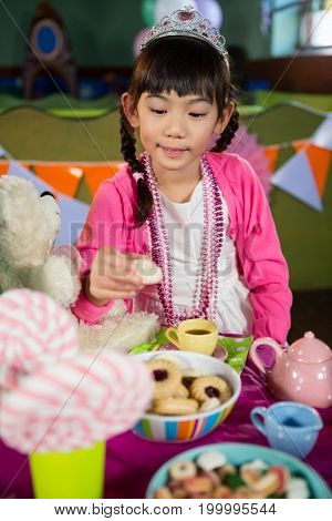 Girl having cookies during birthday party at home