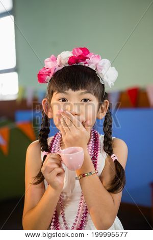 Portrait of cute girl holding teacup during birthday party at home
