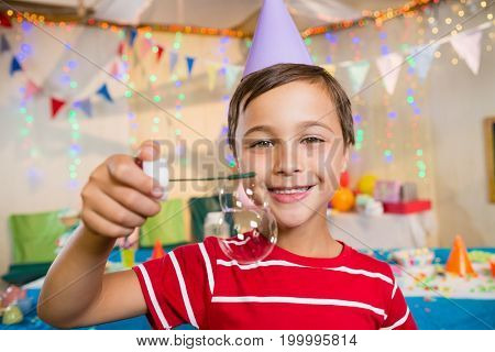 Portrait of cute boy playing with bubble wand during birthday party