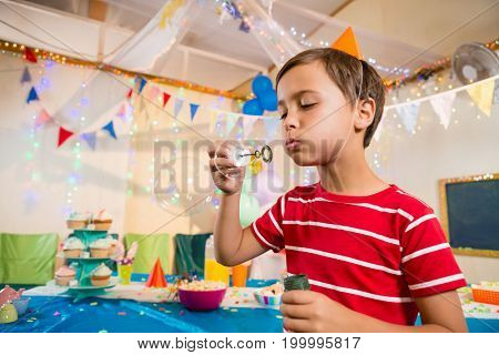 Cute boy playing with bubble wand during birthday party at home