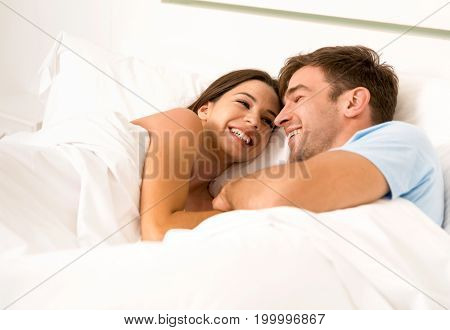 Young couple on bed and having a good time