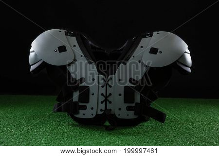 Close-up of American football shoulder pads over artificial turf