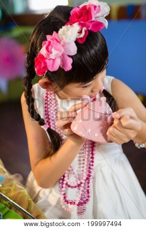Close-up of cute girl holding toy teapot during birthday party at home