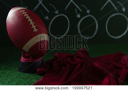 Close-up of American football jersey and football lying on artificial turf against strategy board