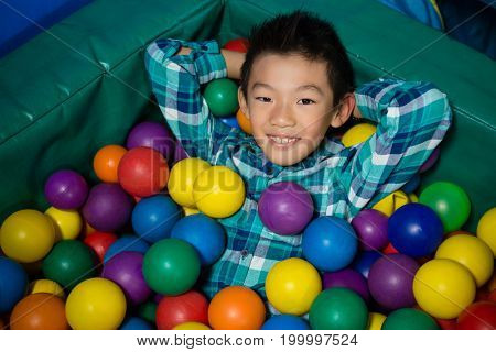 Overhead view of happy boy lying in colorful balls during birthday party