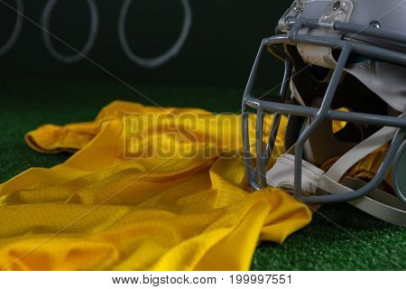 Close-up of American football head gear and jersey lying on artificial turf against strategy board