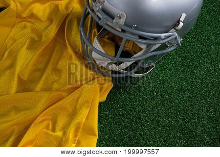 Close-up of American football head gear and jersey lying on artificial turf