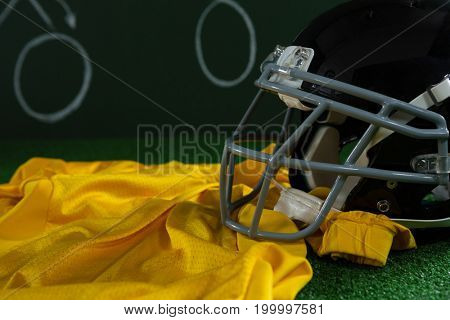 Close-up of American football jersey and head gear lying on artificial turf against strategy board