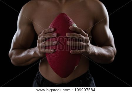 Mid-section of muscular American football player holding a football in his hand