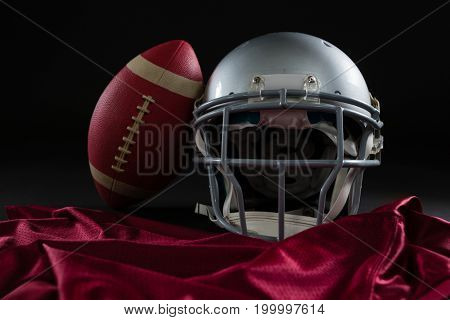 Close-up of American football jersey, head gear and football against black background