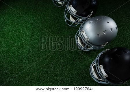 Close-up of American football head gears arranged over artificial turf