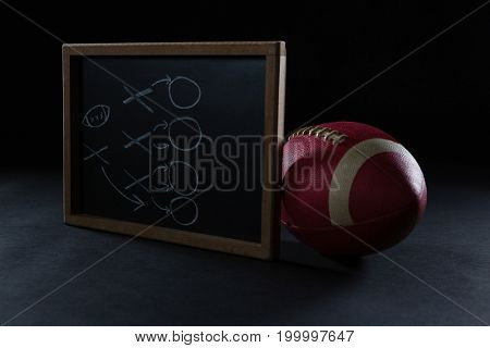 Close-up of game strategy board leaning American football on black background