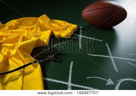 Close-up of American football jersey, whistle and football lying on green board with strategy drawn on it