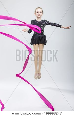 Portrait of Caucasian Female Rhythmic Gymnast In Professional Competitive Black Sparkling Starry Suit Doing Artistic Ribbon Spirals Exercises While Jumping in Studio On White. Vertical Image
