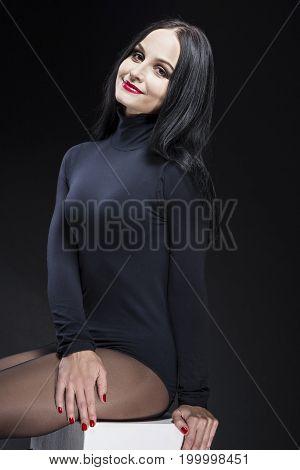 Portrait of Smiling Caucasian Mature Brunette Woman. Posing in Black Body Suit Against Black Background. Vertical Composition