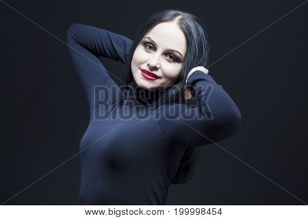 Portrait of Beautiful Relaxed Caucasian Mature Brunette. Posing in Black Body suit Against Black.Lifted Hands Crossed Behind.Horizontal Shot