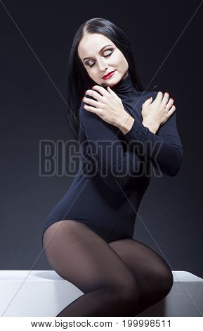 Beauty Ideas. Sexy and Sensual Alluring Caucasian Mature Brunette Woman in Black Body Suit. Posing On White Box Against Black. Vertical Image Composition