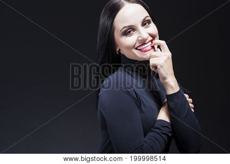Beauty Ideas. Natural Portrait of Smiling Sensual Caucasian Brunette Mature Woman in Black Body Suit. Posing Against Black. Horizontal Image