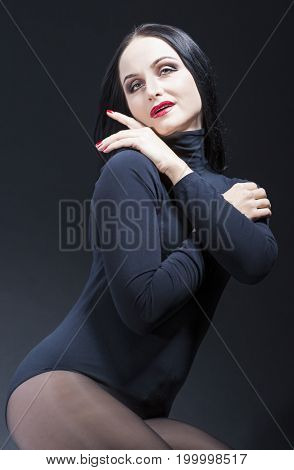 Beauty Ideas. Natural Portrait of Smiling Sensual Caucasian Brunette Mature Woman in Black Body Suit. Posing Against Black. Vertical Image Composition