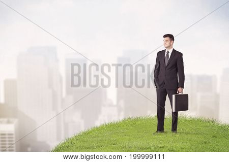 A cheerful caucasian elegant sales manager standing in small green grass in front of faded city landscape, tall buildings concept.