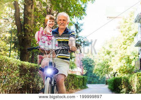 Senior Man Riding Bicycle With Granddaughter