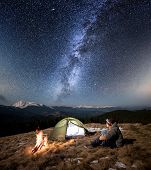 Male tourist have a rest in his camp at night. Man with a headlamp sitting near campfire and tent under beautiful sky full of stars and milky way. On the background snow-covered mountains and forests poster