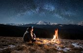 Male tourist have a rest in the mountains at night. Man with a headlamp sitting near campfire under beautiful night sky full of stars and milky way and enjoying night scene poster
