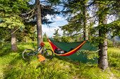 Camping in woods with hammock and sleeping bag on mountain biking adventure trip in green mountains. Travel campsite when mtb cycling with backpack. Lightweight shelter in wilderness forest Poland. poster