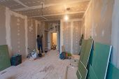 Worker prepares walls for remodeling it by drywall (plasteboard gypsum) and interior of apartment with materials during on the renovation and construction. poster
