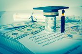 Concept of graduation black cap on roll up Dollars bill with diploma or certificate on letters foreign money US dollars Singapore. Education of competition on abroad program in famous institution. poster