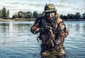 Bearded soldier of special forces in action during river raid in the jungle terrain. He is waist deep in the water and mud and ready to meet enemy, survive and fight in agressive hostile environment poster