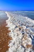 Waves crash along the coast on a beautiful day in Daytona Beach Florida. poster