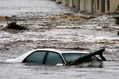 A car caught in a flood and swept away in the raging water poster