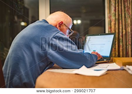 Old Man Using A Laptop Computer To Check His Share Portfolios ,hampshire,england,u.k.