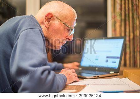Elderly Man Using A Laptop Computer To Check Share Portfolios ,hampshire,england,u.k.