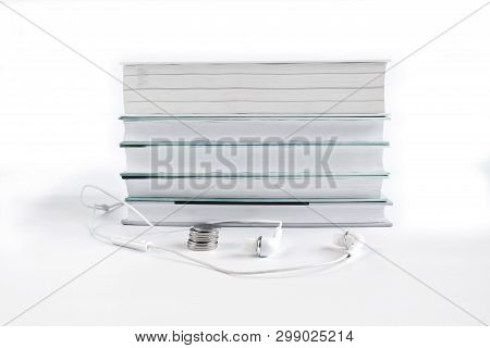Concept Of Cheap Audio Books. White Headphones And Coins Near The Stack Of Books. White Background W