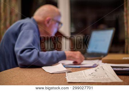 Elderly Man Using A Computer To Check His Share Portfolios ,hampshire,england,u.k.