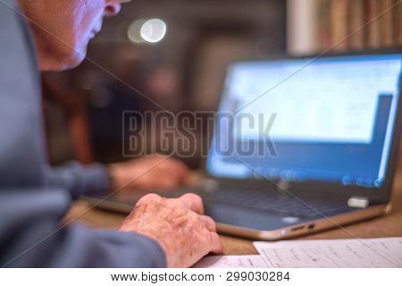 Elderly Man On A Laptop Computer Checks His Online Banking,hampshire,england,u.k.