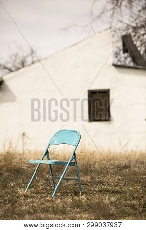 Abandoned Blue Metal Chair In Front Of Dilapidated House