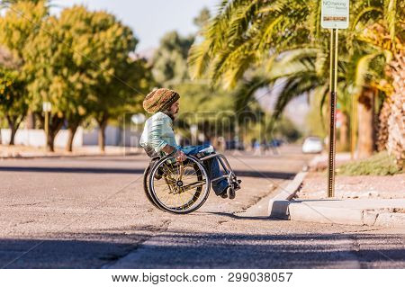 Young Man In Wheelchair Approaches City Curb