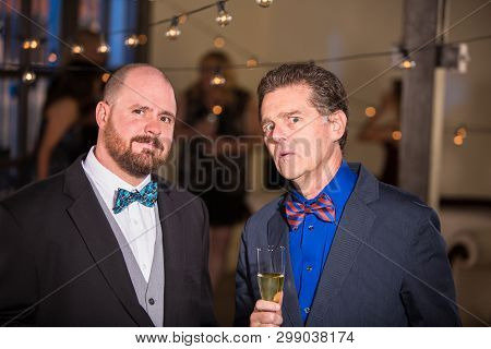 Two Skeptical Men Wearing Bow Ties At A Party