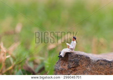 Miniature People: Business Man Reading Newspaper With Copy Space Using As Background Business, Educa